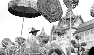 FILE - In this May 5, 1950, file photo, twenty-two-year-old King Bhumibol Adulyadej, in traditional Thai dress, is borne on a palanquin by members of the royal household after his coronation, crowning himself Rama the 9th, in Bangkok, Thailand. Seven decades ago, Thailand's King Bhumibol Adulyadej, then 22, was crowned in ceremonies replete with ancient rituals that will be seen again when his son King Maha Vajiralongkorn ascends the throne on Saturday, May 4, 2019, as King Rama X. (AP Photo/Charles P. Gorry, File)