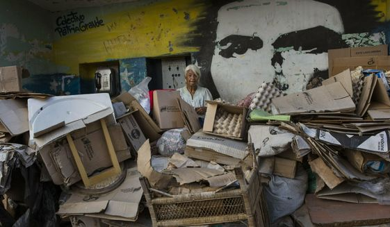 Rosa Maria Gomez, 65, poses for a photo, with a mural of revolutionary leader Ernesto Che Guevara, inside a makeshift shelter in the Petare neighborhood of Caracas, Venezuela, Thursday, May 2, 2019. (AP Photo/Rodrigo Abd)