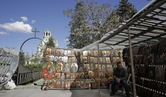 In this photo taken on Tuesday, April 30, 2019, a vendor selling Orthodox icons wait for customers at an open air market near the Alexander Newsky cathedral, in Sofia, Bulgaria, ahead of an upcoming visit by Pope Francis. During his first visit to the Orthodox country of Bulgaria, on May 5 and 6, Pope Francis will visit the capital, Sofia, and the town of Rakovsky, which is home of the largest Catholic community in the Balkan country. (AP Photo/Valentina Petrova)