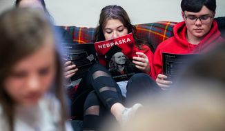 In this Thursday, April 18, 2019 photo, Paige Moore, center, and Ben Baumgartner, right, check guides which they received from Abel Covarrubias, the assistant director of the office of admissions for the University of Nebraska-Lincoln who spoke with sophomores and juniors in Stapleton, Neb. (Brendan Sullivan/Omaha World-Herald via AP)