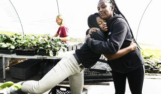 Tamia Coleman, 16, left, hugs Girls Inc. Youth Farm program manager Kenya Ghanor while working in the farm's greenhouse in Friday, April 26, 2019 in Memphis, Tenn. Girls harvest every Friday; for produce sold every Saturday at the Farmers Market. (Mark Weber/The Commercial Appeal via AP)