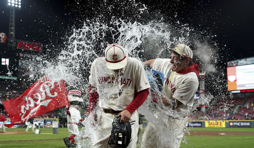 Cincinnati Reds' Nick Senzel, front, is doused byDerek Dietrich, back, after the team's baseball game against the San Francisco Giants, Saturday, May 4, 2019, in Cincinnati. The Reds won 9-2. (AP Photo/Aaron Doster)