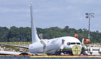 A charter plane carrying 143 people and traveling from Cuba to north Florida sits in a river at the end of a runway, Saturday, May 4, 2019 in Jacksonville, Fla.  The Boeing 737 arriving at Naval Air Station Jacksonville from Naval Station Guantanamo Bay, Cuba, with 136 passengers and seven aircrew slid off the runway Friday night into the St. Johns River, a NAS Jacksonville news release said. (AP Photo/Gary McCullough)