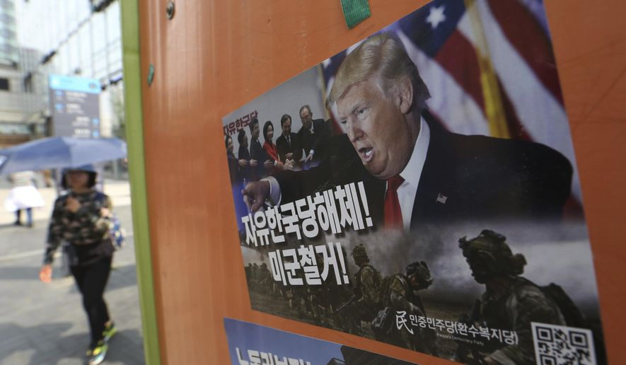 "A poster showing a portrait of U.S. President Donald Trump is displayed to demand withdrawal of U.S. troops from Korea peninsular on the street in Seoul, South Korea, Saturday, May 4, 2019. North Korea on Saturday fired several unidentified short-range projectiles into the sea off its eastern coast, the South Korean Joint Chiefs of Staff said, a likely sign of Pyongyang's growing frustration at stalled diplomatic talks with Washington meant to provide coveted sanctions relief in return for nuclear disarmament. The signs read: ""Withdrawal of U.S. troops."" (AP Photo/Ahn Young-joon)"