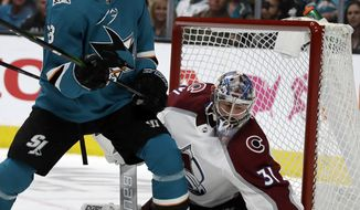 San Jose Sharks' Melker Karlsson, left, watches as Colorado Avalanche goalie Philipp Grubauer (31) gloves the puck during the first period of Game 5 of an NHL hockey second-round playoff series Saturday, May 4, 2019, in San Jose, Calif. (AP Photo/Ben Margot)