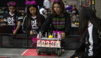 In this Thursday, April 25, 2019 photo, Seventh and eighth graders Amisha Chandra (far left), Elina Kim, Olivia Ramirez, Kristina Tu, of the Orchard Hills, Calif RoboHawks team practice before their first competition of the VEX World Robotics Championships in Louisville Ky. (Michelle Hutchins/Courier Journal via AP)