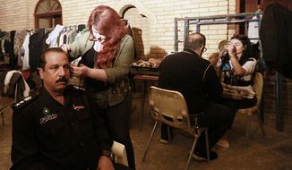 """In this Friday, April 26, 2019, photo, Iraqi actors prepare to perform their roles in """"The Hotel,"""" at a filming location in Baghdad, Iraq. A Baghdad studio is filming Iraq's first TV drama in 7 years, as the arts come to life again in the capital after more than a decade of war. (AP Photo/Hadi Mizban)"""
