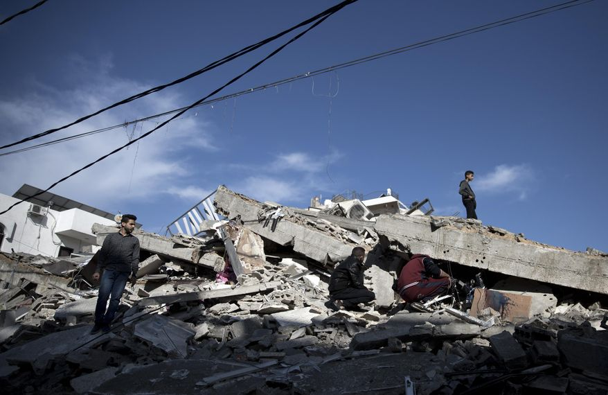 Palestinians check the damage of a multi-story building following Israeli airstrikes in Gaza City, Sunday, May 5, 2019. Palestinian militants on Saturday fired over 200 rockets into Israel, drawing dozens of retaliatory airstrikes on targets across the Gaza Strip in a round of intense fighting that broke a monthlong lull between the bitter enemies. (AP Photo/Khalil Hamra)