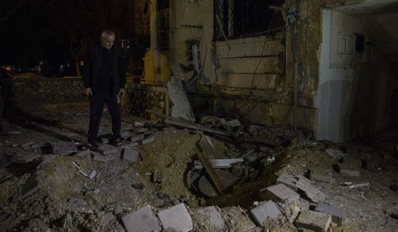 A man stands outside his building after it was hit by a rocket fired from Gaza in the costal city of Ashkelon, Israel, Sunday, May 5, 2019. Palestinian militants fired over 250 rockets into Israel, drawing dozens of retaliatory airstrikes on targets across the Gaza Strip in a round of intense fighting that broke a month-long lull between the bitter enemies (AP Photo/Tsafrir Abayov)
