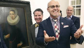 """A Los Angeles couple, Craig Gilmore, right, and David Crocker, pose in front of a 17th painting, """"Portrait of a Lady"""" by the Flemish artist Melchior Geldorp at the National Museum in Warsaw, Poland, Friday, April 5, 2019. The two were dumbfounded when Homeland Security agents showed up at their home in 2016 with news the work been looted by the Nazis from Poland's National Museum during World War II. (AP Photo/Czarek Sokolowski)"""