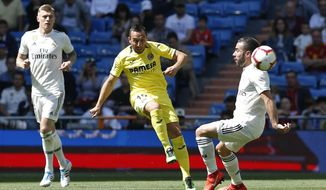 Villarreal's Santi Cazorla, centre, kicks the ball past Real Madrid's Dani Carvajal, right, during a Spanish La Liga soccer match between Real Madrid and Villarreal at the Santiago Bernabeu stadium in Madrid, Spain, Sunday, May 5, 2019. (AP Photo/Paul White)