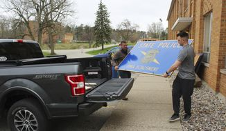 In this Tuesday, April 30, 2019 photo, Michigan State Police Lt. Christian Clute, left, and Trooper Colin Gensterblum carry an Ionia detachment sign from the old Riverside Correctional Facility to Clute's pickup truck during moving day. After operating out of an old Riverside Correctional Facility building for more than a decade, the Ionia detachment is relocating three miles north to the Ionia County Central Dispatch. (Elisabeth Waldon/The Daily News via AP)