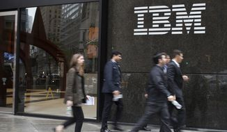 In this Wednesday, April 26, 2017 photo, pedestrians walk past the IBM logo displayed on the IBM building in Midtown Manhattan. (AP Photo/Mary Altaffer)