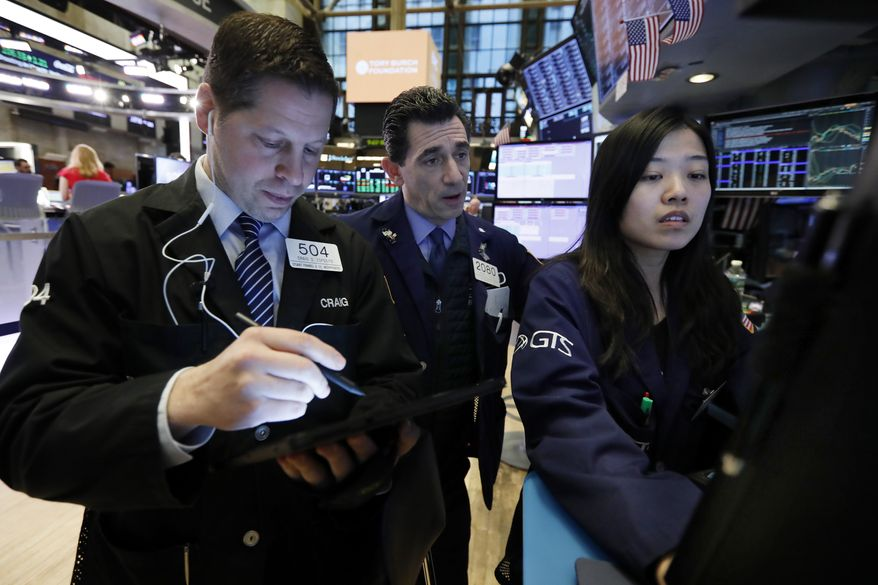 FILE - In this March 18, 2019, file photo trader Craig Esposito, left, works with specialists Peter Mazza, center, and Vera Liu on the floor of the New York Stock Exchange. Stocks fell broadly on Wall Street in afternoon trading Monday, May 6, after President Donald Trump threatened to escalate the trade war between the U.S. and China. (AP Photo/Richard Drew, File)