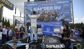 Driver Martin Truex Jr. (19) celebrates with his team after winning the NASCAR Cup Series auto race, Monday, May 6, 2019, at Dover International Speedway in Dover, Del. (AP Photo/Will Newton)