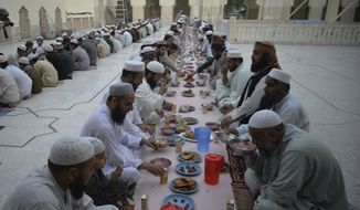 In this photo, Pakistani Muslims wait to break their fast during the fasting month of Ramadan at a mosque in Peshawar, Pakistan, Monday, May 6, 2019. Muslims around the world are observing Ramadan, the holiest month in Islamic calendar. (AP Photo/Muhammad Sajjad) **FILE**
