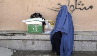 An Afghan woman receives free food donated by King Salman Humanitarian Aid and Relief Center, ahead of the upcoming holy fasting month of Ramadan in Kabul, Afghanistan, Sunday, May 5, 2019. Muslims throughout the world celebrate the holy fasting month of Ramadan, refraining from eating, drinking, and other pleasures from sunrise to sunset. (AP Photo/Rahmat Gul)