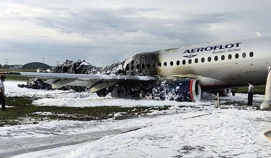 The Sukhoi SSJ100 aircraft of Aeroflot airlines is covered in fire retardant foam after an emergency landing in Sheremetyevo airport in Moscow, Russia, Sunday, May 5, 2019. Scores of people died when the Aeroflot airliner burst into flames while making the emergency landing at the airport Sunday evening, officials said. (Moscow News Agency photo via AP)
