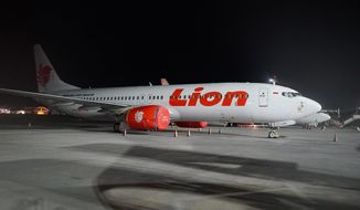This April 13, 2019, photo shows Lion Air's Boeing 737 Max 8 on the tarmac at Ngurah Rai International Airport in Bali, Indonesia. Asian airlines are cutting routes, revamping their schedules and leasing extra aircraft to fill the gaps left by groundings of Boeing 737 Max 8s after deadly crashes in Indonesia and Ethiopia killed 346 people. (AP Photo/Nicole Evatt)