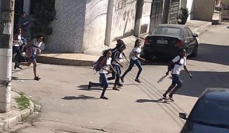 In this photo released by Leonardo Alves, students run from their school, during a shootout between police and suspected drug traffickers in the Mare shantytown of Rio de Janeiro, Brazil, Monday, May 6, 2019. Brazilian officials say an anti-crime operation by police resulted in eight people being killed during the shootout. (AP Photo/Leonardo Alves)