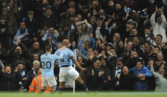 Manchester City's Vincent Kompany, second left, celebrates with Manchester City's Bernardo Silva after scoring his side's opening goal during the English Premier League soccer match between Manchester City and Leicester City at the Etihad stadium in Manchester, England, Monday, May 6, 2019. (AP Photo/Rui Vieira)