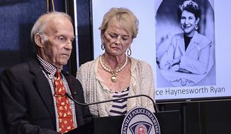 Joe Ryan, left, of Greenville stands with his wife near a photo of his late mother Alice Haynesworth Ryan, during a city police announcement of an arrest in the 1988 cold case homicide in Greenville Monday, May 6, 2019. Police arrested suspect Brian Keith Munns.  (Ken Ruinard/The Independent-Mail via AP)