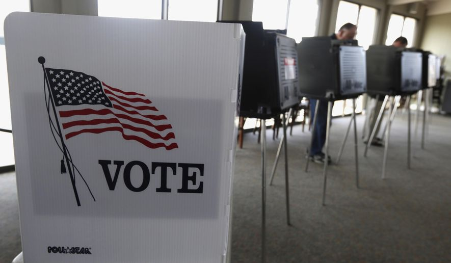 In this March 18, 2014, file photo, voters cast their ballots in Hinsdale, Ill. (AP Photo/M. Spencer Green, File)