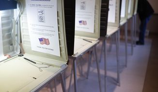 In this Nov. 8, 2016, file photo a lone voter fills out a ballot alongside a row of empty booths at a polling station in the Terrace Park Community Building on Election Day in Cincinnati. (AP Photo/John Minchillo, File)