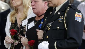Deborah Edenhofer, center, mother of Tyler Edenhofer, prepares to place a rose on the fallen officers memorial during the annual Department of Public Safety Officer Memorial Ceremony, Monday, May 6, 2019, in Phoenix. During the ceremony a plaque was added for 24-year-old Tyler Edenhofer to be displayed with the 29 other troopers who have been killed on the job since 1958. (AP Photo/Matt York)