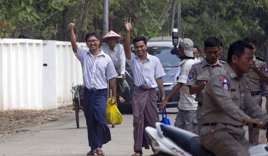 Reuters journalists Wa Lone, left, and Kyaw She Oo, third left, wave as they walk out from Insein Prison after being released in Yangon, Myanmar Tuesday, May 7, 2019. The chief of Yangon's Insein Prison said two Reuters journalists who were imprisoned for breaking the country's Officials Secrets Act have been released. (AP Photo/Thein Zaw)