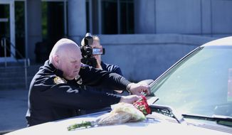 Biloxi Police Chief John Miller places flowers and a card on the police SUV of Officer Robert McKeithen, outside the station in Biloxi, Miss., Monday, May 6, 2019. McKeithen was killed in the line of duty outside the Biloxi Police Department, Sunday night. A manhunt is underway to find the suspect, who shot McKeithen multiple times, police say. (Justin Mitchell/The Sun Herald via AP)