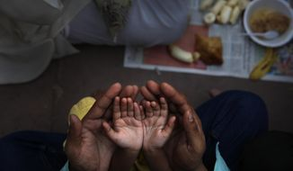 FILE - In this June 30, 2014 file photo, an Indian Muslim father holds the hands of his daughter in his palms and prays before breaking fast on the first day of holy month Ramadan at the Jama Mosque in New Delhi, India. Most Muslims around the world began fasting on Monday, May 6, 2019, for the start of the month of Ramadan. (AP Photo/Manish Swarup, File)