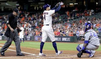 Houston Astros designated hitter George Springer (4) crosses the plate between umpire Pat Hoberb, left, and Kansas City Royals catcher Martin Maldonado, right, after hitting a home run during the first inning of a baseball game Monday, May 6, 2019, in Houston. (AP Photo/Michael Wyke)