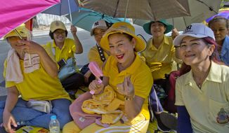 Thai people sit on a side-road, anticipating access to Suddhaisavarya Prasad Hall, in which Thailand's King Maha Vajiralongkorn scheduled to grant a public audience in Bangkok, Thailand, Monday, May 6, 2019. King Maha Vajiralongkorn was officially crowned amid the splendor of the country's Grand Palace, taking the central role in an elaborate centuries-old royal ceremony that was last held almost seven decades ago.(AP Photo/Gemunu Amarasinghe)