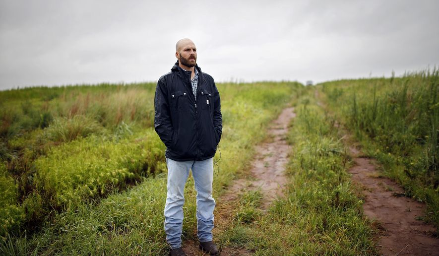 FILE - In this July 17, 2014, file photo, Michael Behenna stands on land that he helps work in Medford, Okla. The White House announced Monday, May 6, 2019, that President Donald Trump pardoned Behenna, a former U.S. soldier convicted in 2009 of killing an Iraqi prisoner. (Sarah Phipps/The Oklahoman via AP, File)