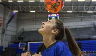 """FILE - In this Saturday, March 23, 2019, file photo, Macarena Sanchez, a soccer player who is taking legal action against her club and the Argentine soccer association for not recognizing her as a professional player, heads a ball before a mixed soccer match as part of the """"I play for equality"""" event in Buenos Aires, Argentina. Players in Latin America face obvious economic and cultural challenges when it comes to soccer and sports overall. (AP Photo/Daniel Jayo, File)"""