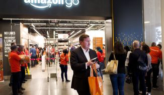 A customer carries his shopping bag as she walks out of a newly-opened Amazon Go store, Tuesday, May 7, 2019 in New York. The store will be the first Amazon Go store to accept cash. At its other shops, customers can only enter with an app that links to a credit card or an Amazon account.(AP Photo/Mark Lennihan)