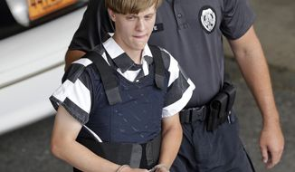 FILE - In this June 18, 2015 file photo, Charleston, S.C., shooting suspect Dylann Roof is escorted from the Cleveland County Courthouse in Shelby, N.C.  Survivors and relatives of nine people killed in a racist attack at a South Carolina church have asked a federal appeals court to reinstate their lawsuit over a faulty background check that allowed Roof to buy the gun he used in the 2015 shooting. A judge dismissed the lawsuit last year. The 4th U.S. Circuit Court of Appeals heard arguments Tuesday, May 7, 2019. (AP Photo/Chuck Burton, File)