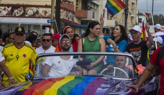 FILE - In this May 12, 2018 file photo, Mariela Castro, daughter of Raul Castro and director of Cuba's National Center for Sexual Education, waves a rainbow flag while sitting in a convertible car during the annual Gay Pride parade in Havana, Cuba. Castro said Tuesday, May 7, 2019, that the Cuban government has cancelled the Conga Against Homophobia parade, that was widely seen as a sign of progress on gay rights. (AP Photo/Desmond Boylan)