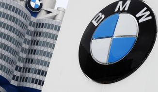 FILE-In this March 21, 2018 file photo shows the logo of German car manufacturer BMW visible at the headquarters in Munich, Germany. German automaker BMW said Tuesday that its first quarter profit sagged by 74 percent as earnings were hit by a 1.4 billion-euro ($1.6 billion) set-aside for an anti-trust fine from the European Commission and by higher up-front costs for new technology and factories.(AP Photo/Matthias Schrader)