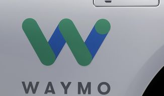 FILE - In this May 8, 2018, file photo, a Waymo logo is displayed on the door of a car at the Google I/O conference in Mountain View, Calif. Google's self-driving car spinoff Waymo is teaming up with Lyft in Arizona to attempt to lure passengers away from ride-hailing market leader Uber. (AP Photo/Jeff Chiu, File)