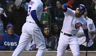 Chicago Cubs' Kris Bryant left, celebrates with teammate Willson Contreras after scoring on a Javier Baez sacrifice fly during the first inning of a baseball game against the Miami Marlins, Tuesday, May 7, 2019, in Chicago. (AP Photo/Paul Beaty)