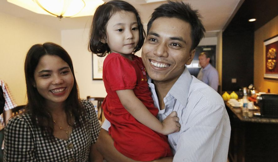 Reuters journalist Kyaw Soe Oo celebrates with wife Chit Su Win and their daughter after being released from prison after a presidential pardon, Wednesday, May 7, 2019, in Yangon, Myanmar. The two journalists Wa Lone, 32, and Kyaw Soe Oo, 28, were imprisoned for breaking Myanmar's Official Secrets Act over reporting on security forces' abuses of Rohingya Muslims were pardoned Tuesday, the prison chief and witnesses said. (Ann Wang/Pool Photo via AP)