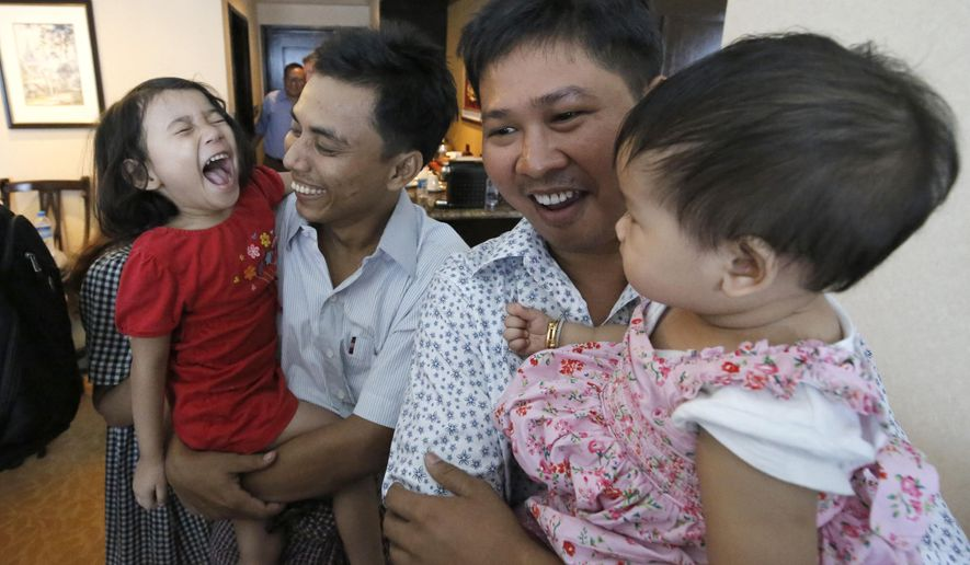 Reuters reporters Wa Lone, center right, and Kyaw Soe Oo hold their children after being freed from prison, in Yangon, Myanmar, Tuesday, May 7, 2019. The two journalists who were imprisoned for breaking Myanmar's Official Secrets Act over reporting on security forces' abuses of Rohingya Muslims were pardoned and released Tuesday. (Ann Wang/Pool Photo via AP)