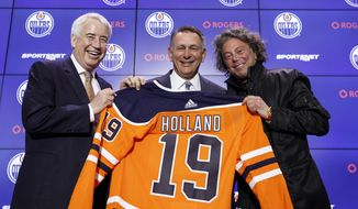 Bob Nicholson, CEO and Vice-Chair of the Edmonton Oilers NHL hockey team, left, and team owner Daryl Katz, right, flank new general manager Ken Holland, after announcing the hire in Edmonton, Alberta, Tuesday, May 7, 2019. (Jason Franson/The Canadian Press via AP)