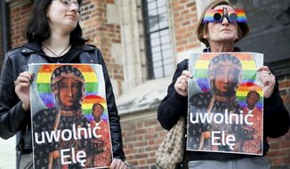 """In this photo taken in Krakow, Poland, May 6, 2019, picketers with posters of Poland's most-revered icon of Mother of God of Czestochowa with the LGBT rainbow colors added to its halos, protest the detention for a few hours of Elzbieta Podlesna, on suspicion she put up such posters near a church in the city of Plock. An inscription on the poster entitled """"Unleash Elzbiete"""". (AP Photo/Beata Zawrzel) Poland Out"""
