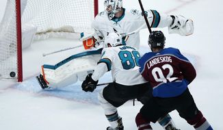 San Jose Sharks goaltender Martin Jones, back, makes a kick-save of a shot as defenseman Brent Burns, center, and Colorado Avalanche left wing Gabriel Landeskog pursue the puck in the first period of Game 6 of an NHL hockey second-round playoff series Monday, May 6, 2019, in Denver. (AP Photo/Jack Dempsey) ** FILE **