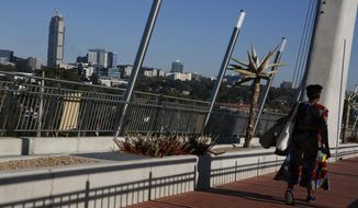 In this May 4, 2019, photo, a woman makes her way toward Johannesburg suburb of Sandton, background, on a pedestrian bridge that connects it to the black township of Alexandra. Twenty-five years after the end of apartheid, the neighboring suburbs are a stark example of how inequality is still on display in South Africa. (AP Photo/Denis Farrell)