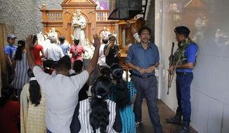 A Sri Lankan naval soldier stands guard as Catholic devotees pray at the St. Anthony's church after it was partially opened for the first time since Easter Sunday attacks, in Colombo, Sri Lanka, Tuesday, May 7, 2019. Two bomb experts were among the suicide attackers who struck churches and hotels on Easter in Sri Lanka and all those directly involved in the bombings are either dead or under arrest, police said. (AP Photo/Eranga Jayawardena)