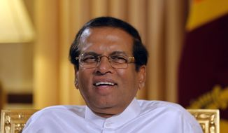 """Sri Lankan President Maithripala Sirisena smiles during an interview with the Associated Press at his residence in Colombo, Sri Lanka, Tuesday, May 7, 2019. Sirisena  says """"99%"""" of the suspects in Easter Sunday attacks on churches and hotels have been arrested and their explosive materials seized. (AP Photo/Eranga Jayawardena)"""